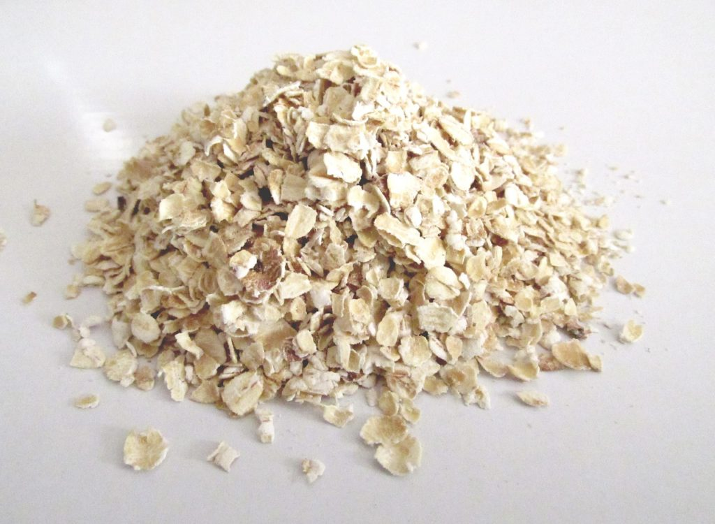 Handful of bulk rolled oats on a table.