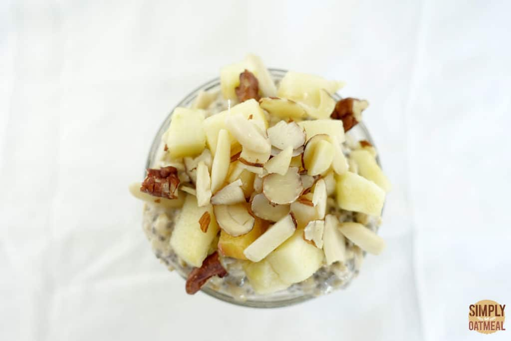 Closeup of diced apple and sliced almonds. The oatmeal toppings are covering the top of overnight oats in a bowl.