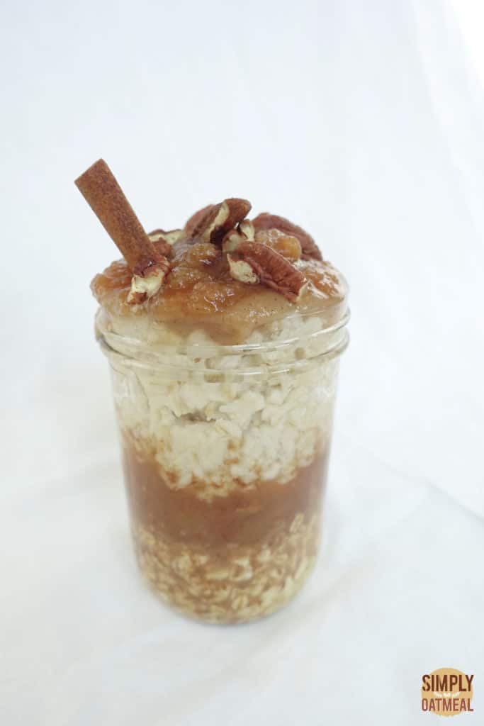 One serving of apple cider overnight oats in a tall glass container.
