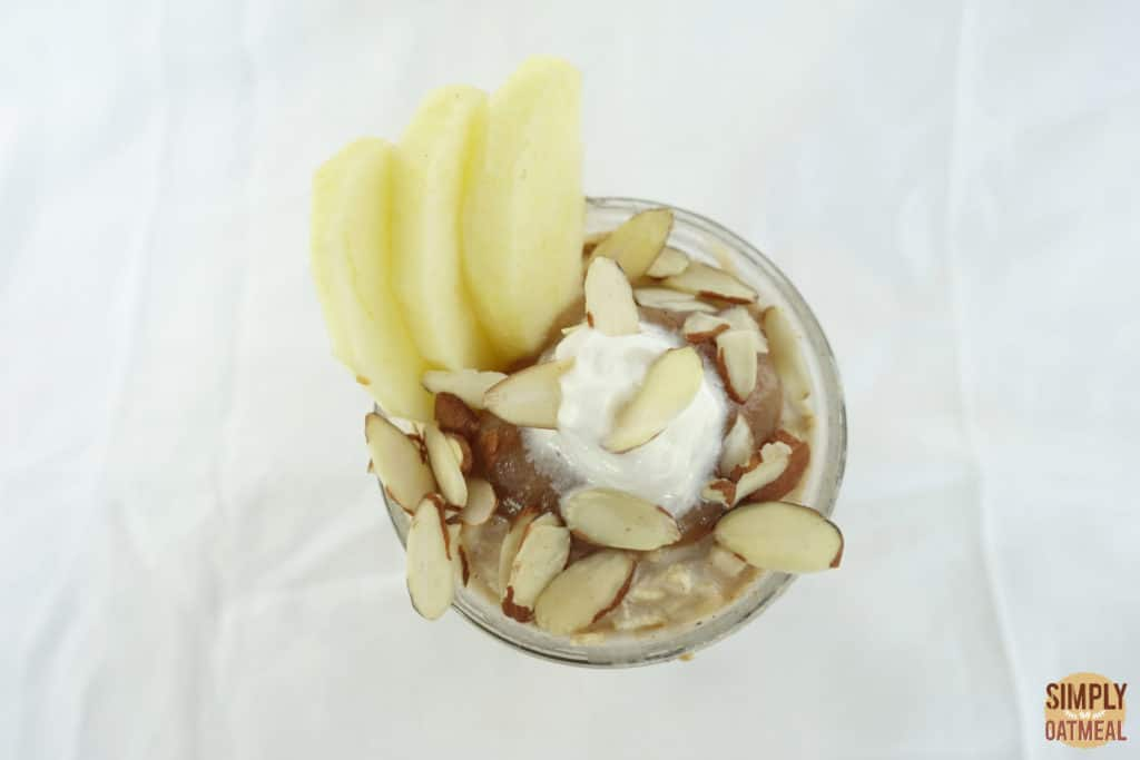 Slivered almonds, whipped creams and sliced apples on top of apple cinnamon overnight oats