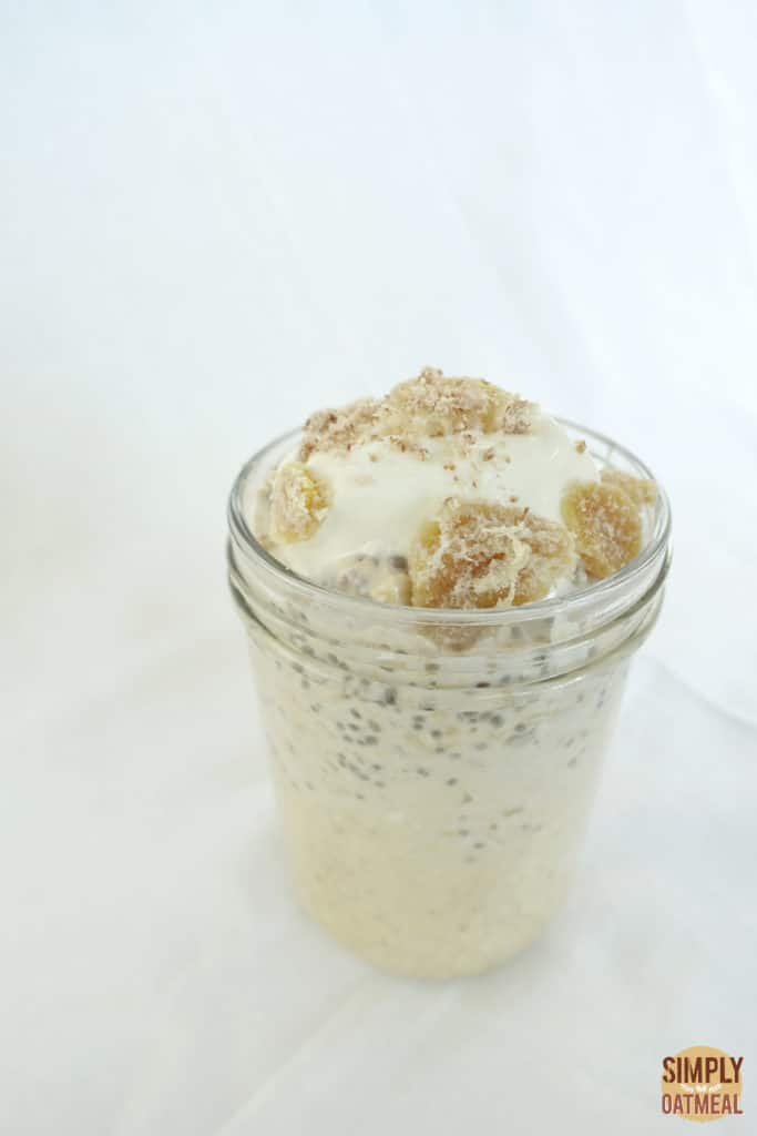 A serving of apple ginger overnight oats in a tall glass container.
