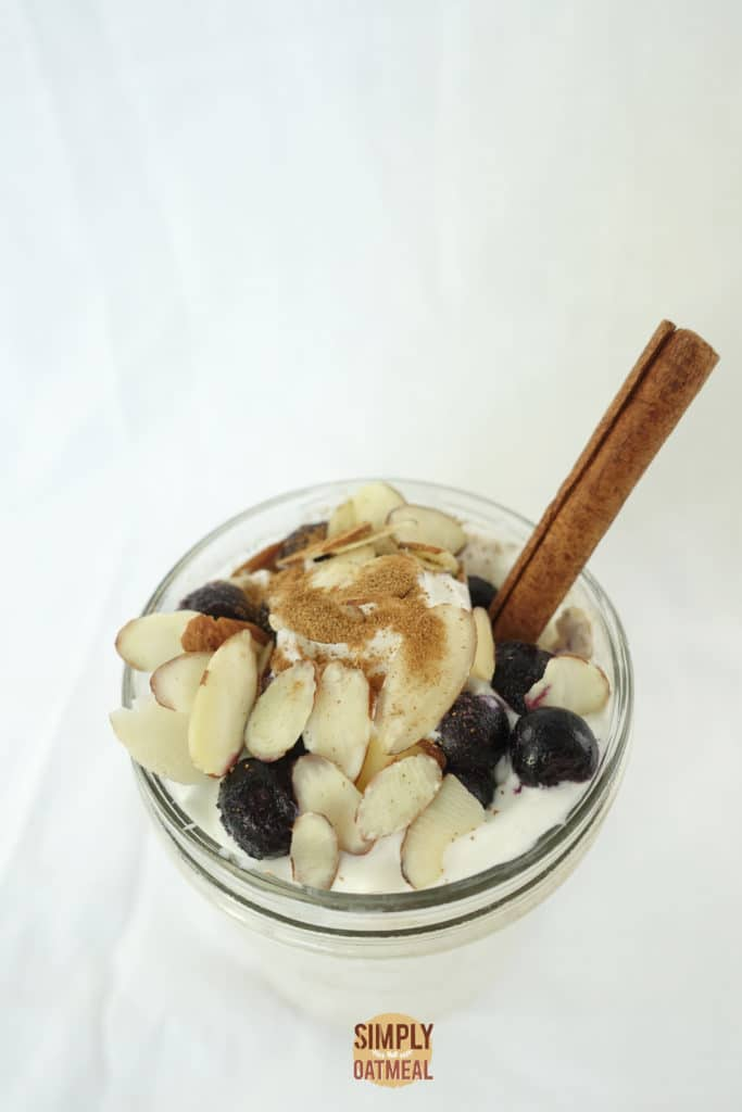 Top view of a mason jar filled with apple pie overnight oats. The oatmeal toppings include slivered almonds, fresh blueberries and a cinnamon stick.