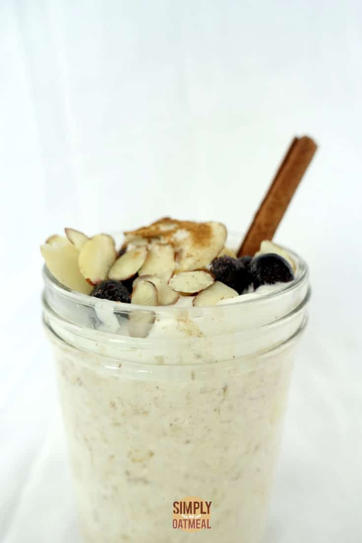 A single serving of apple pie overnight oats in a mason jar. The soaked oats are topped with whipped cream, fresh blueberries, slivered almonds and a sprinkle of cinnamon.