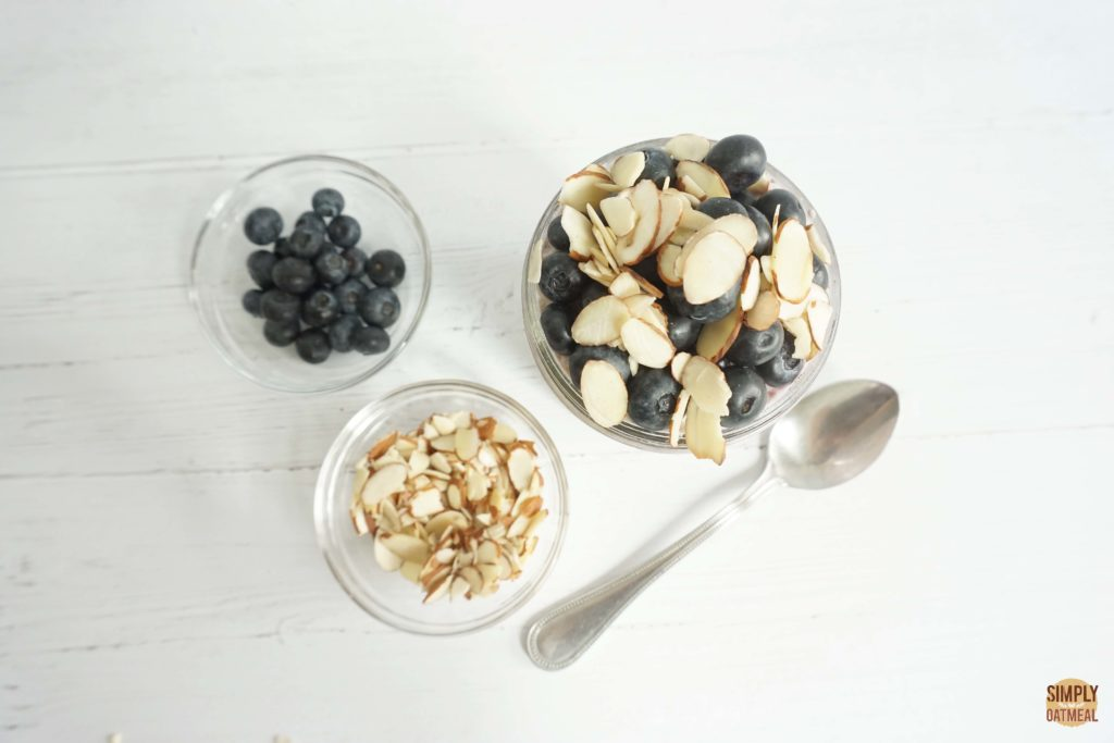 Sliced almonds, fresh blueberries and overnight oatmeal in a glass bowl.