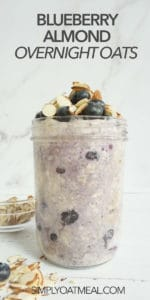 Single portion of blueberry almond overnight oats in a tall glass jar. The oatmeal is topped with almonds and fresh blueberries.