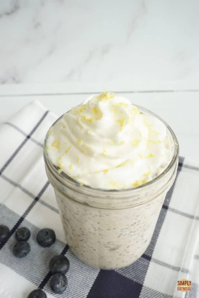 Bowl of blueberry lemon overnight oats topped with fresh lemon zest