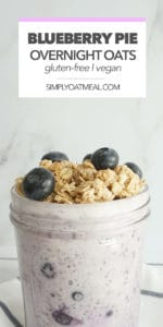 Serving of blueberry pie overnight oats in a glass bowl with fresh blueberries and crunchy pie topping