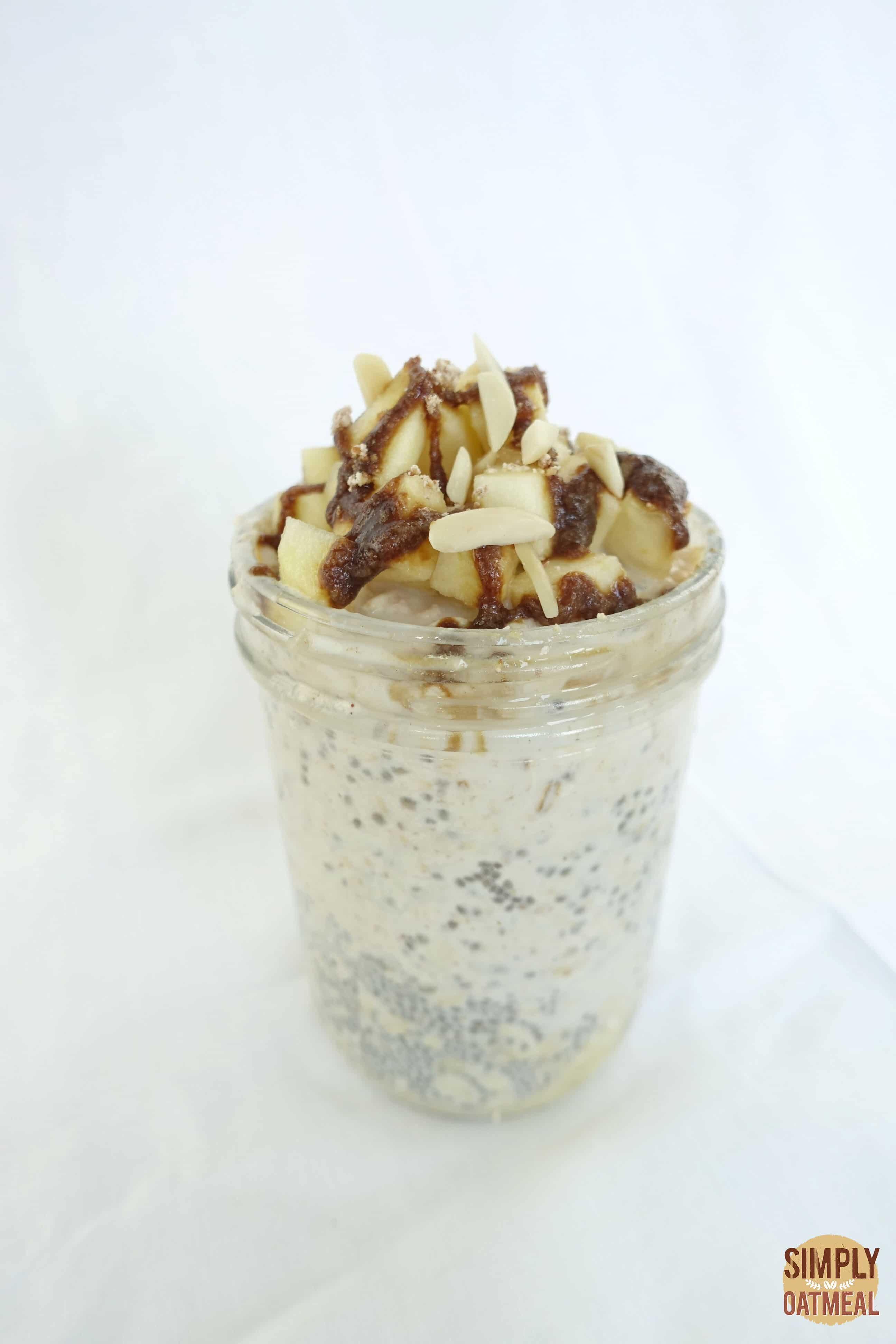 Single serving of caramel apple overnight oats in a tall glass container.