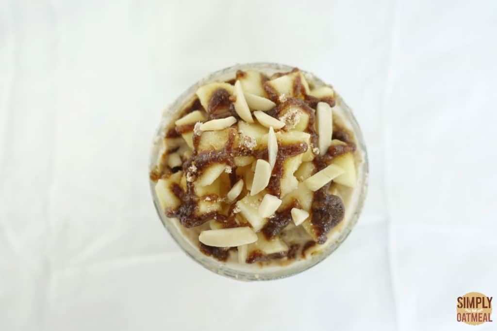 The overnight oats are topped with chopped fresh apple, caramel and slivered almonds.