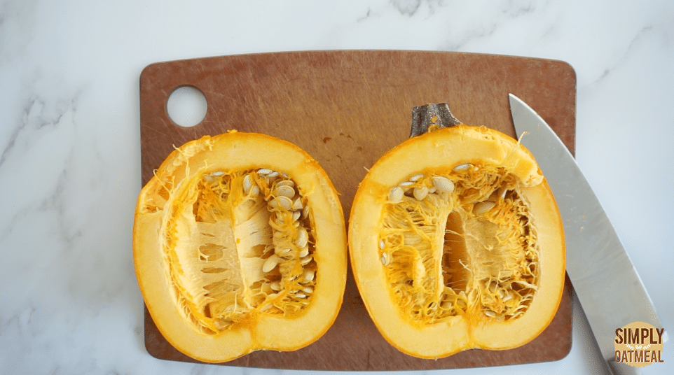 Pumpkin cut in half on cutting board with a large knife.