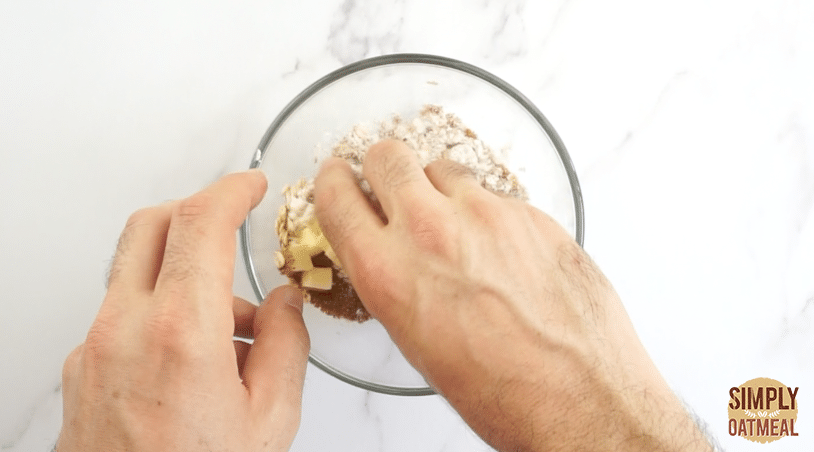 Use your fingertips to work the butter into the oatmeal crumble topping. The cold butter should be worked into pea-sized crumbles inside the mixture.