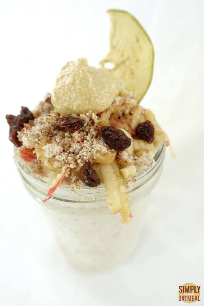 One serving of grated apple overnight oats topped with raisons, peanut butter and an apple chip.