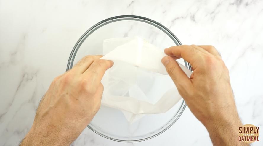 Nut milk bag placed inside a large glass bowl