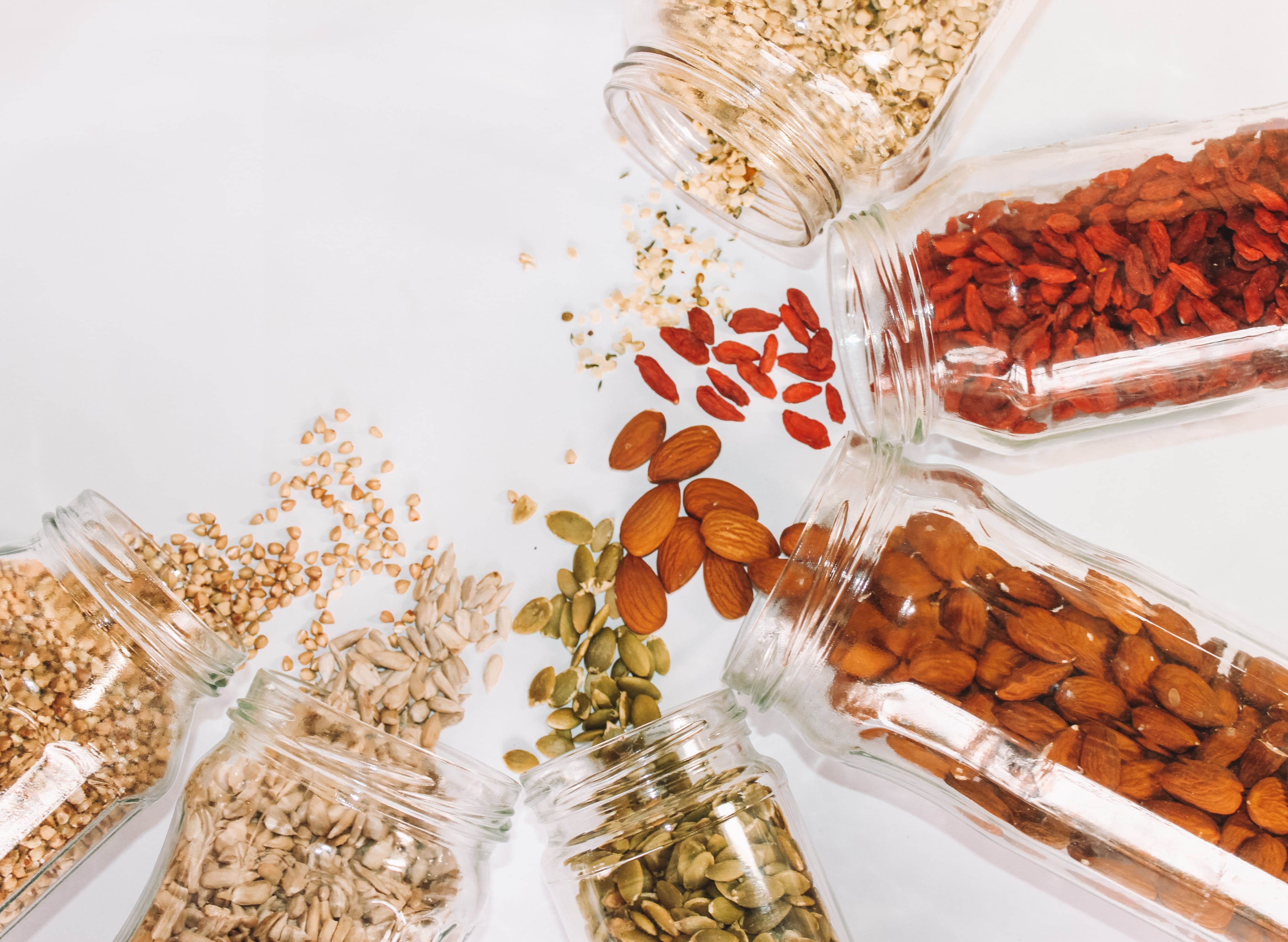 Glass jars filled with almonds, gogi berries, pepita seeds, sunflower seeds and many more oatmeal toppings.