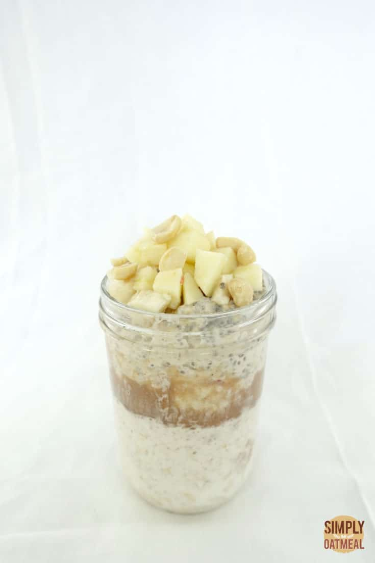 Overnight oats and peanut butter layered in a tall glass container topped with fresh chopped apple and peanuts.
