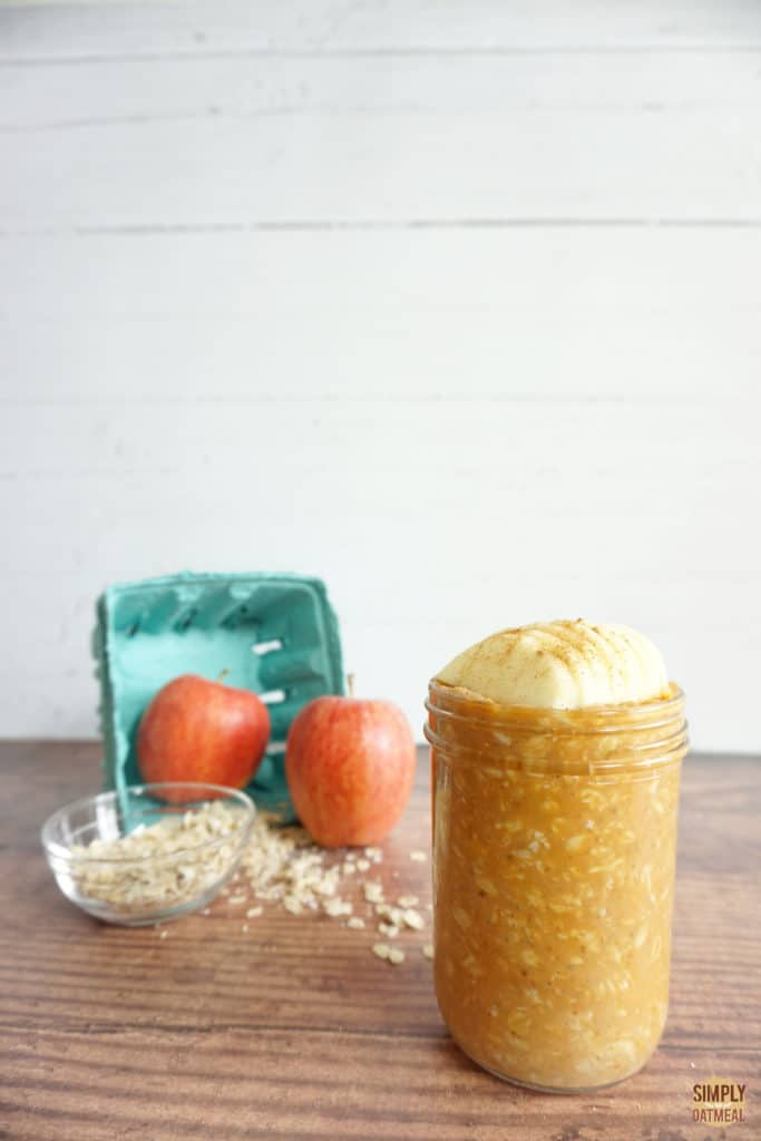 Pumpkin apple overnight oats in a glass jar. Whole apples and raw oats in the background.