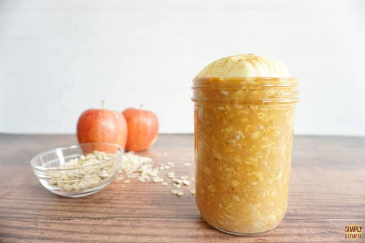 Pumpkin apple overnight oats in a glass container. 2 whole apples and small bowl of raw oats in the background.