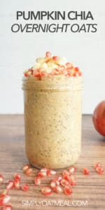 Pumpkin chia overnight oats served in tall glass jar. Oatmeal toppings include cubed apple and pomegranate seeds