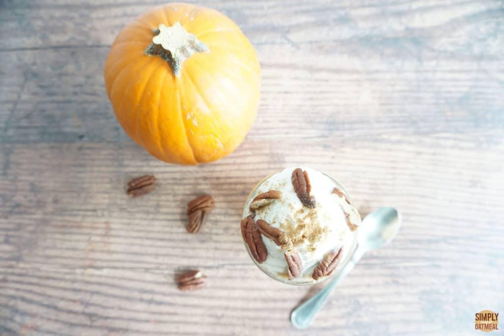 pumpkin pie overnight oats in a small bowl next to a whole sugar pie pumpkin