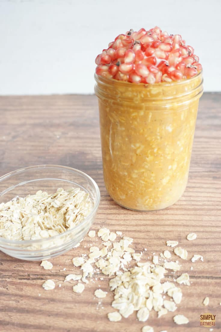pumpkin puree overnight oats topped with pomegranate seeds. Rolled oats are sprinkled across the wood table
