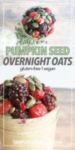 Roasted pumpkin seeds and mixed berries on top of pumpkin seed overnight oats in a small glass bowl.