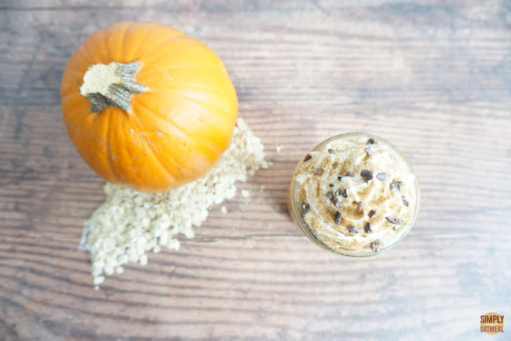 pumpkin spice latte overnight oats in a small glass bowl with a whole pie pumpkin on the side