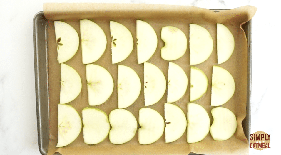 raw apple slices spread out evenly on a baking sheet.
