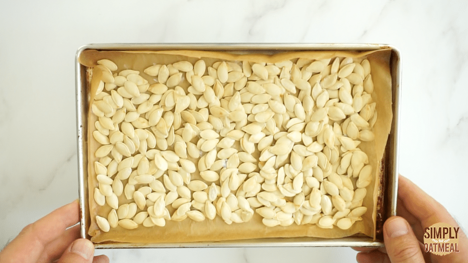 roasted pumpkin seeds taken from the hot oven. Even roasted with a slight toasted color.