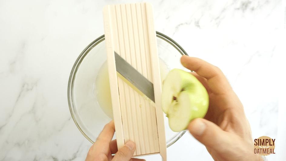 Slice apple using mandoline to make consistent even apple chips