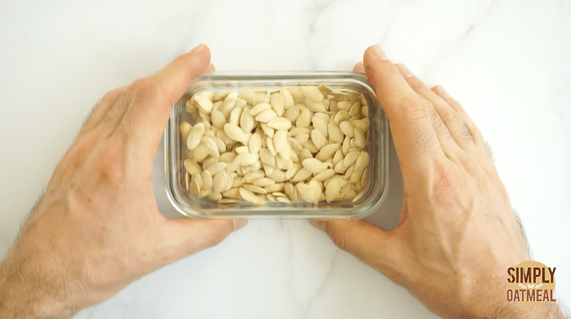 Roasted pumpkin seeds being stored in a glass container. The seeds have fully cooled and while last about 2 weeks.