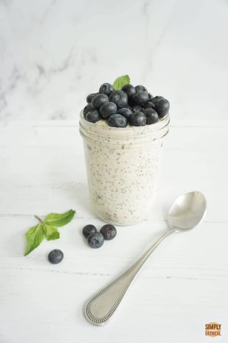 Single serving of blueberry muffin overnight oats in a mason jar. The oatmeal is topped with a pile of fresh blueberries and mint sprig
