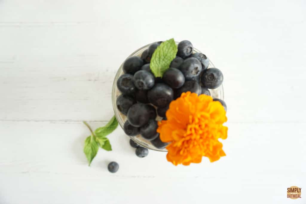 Blueberry muffin overnight oatmeal topped with fresh blueberries and an edible flower.