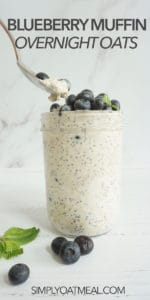 Single serving of blueberry muffin overnight oats in a glass jar. Fresh blueberries and mint are laying on the surface of the table