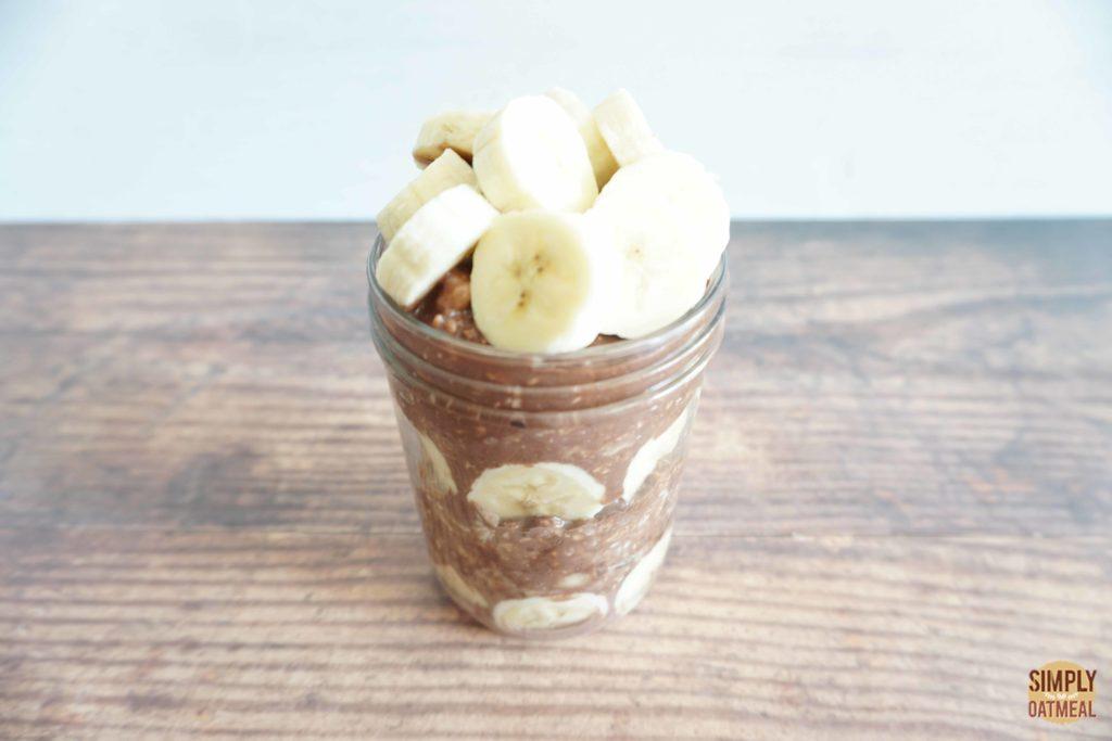 Chocolate banana overnight oats topped with slices of fresh banana.