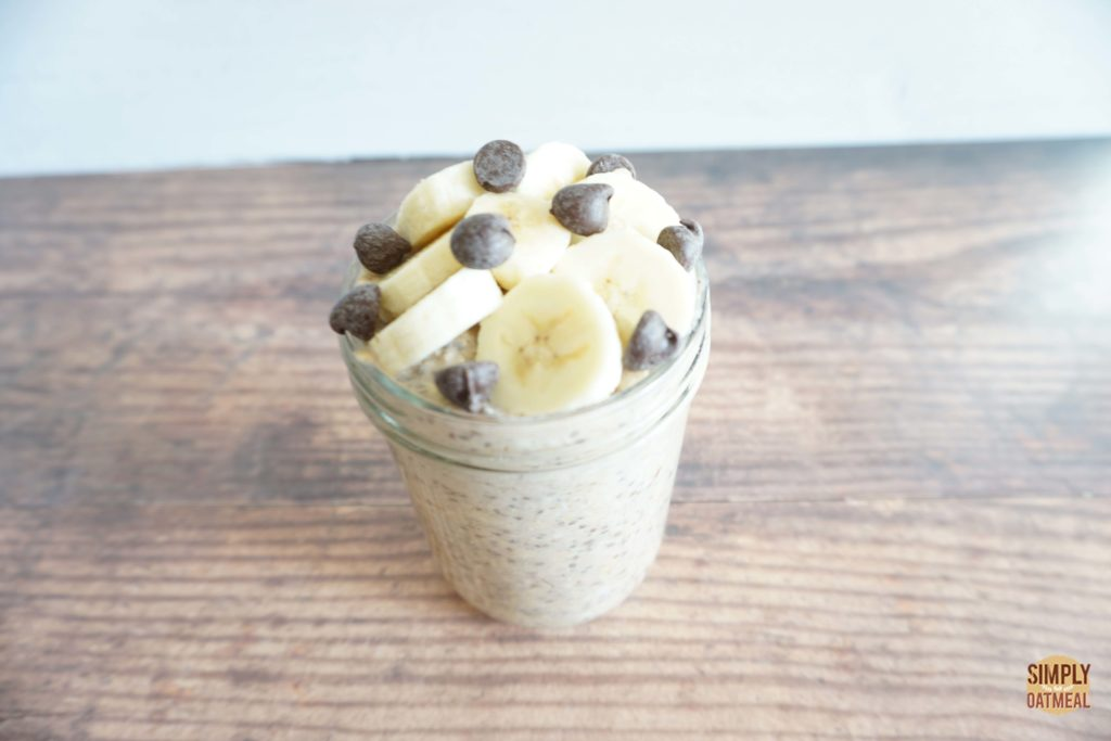 Chocolate chips and banana slices on top of overnight oats in a glass bowl.