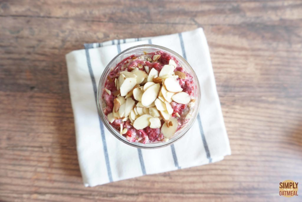 Raspberry almond overnight oats topped with raspberries and sliced almonds