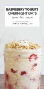 Glass bowl with a serving of raspberry yogurt overnight oats garnished with raspberries, yogurt and granola.