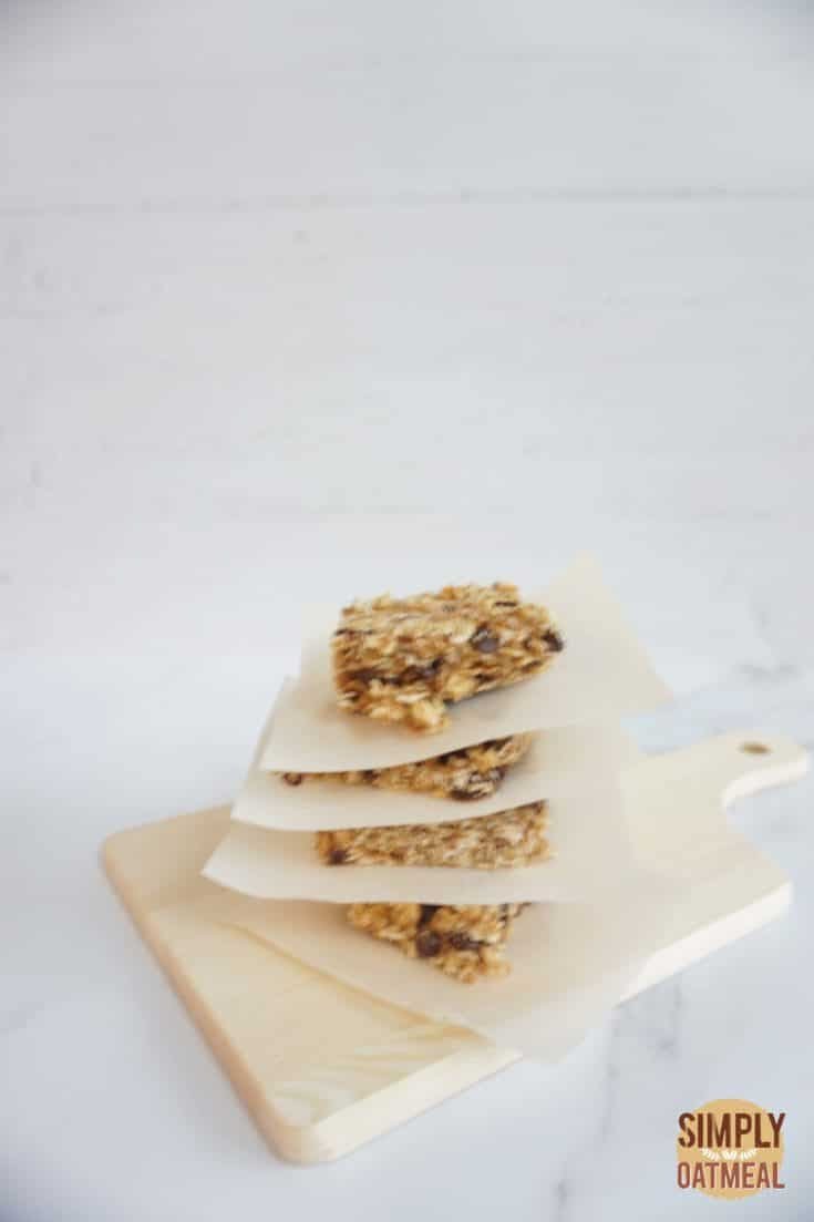 No bake oatmeal raisin bars stacked on top of each other with parchment paper in between