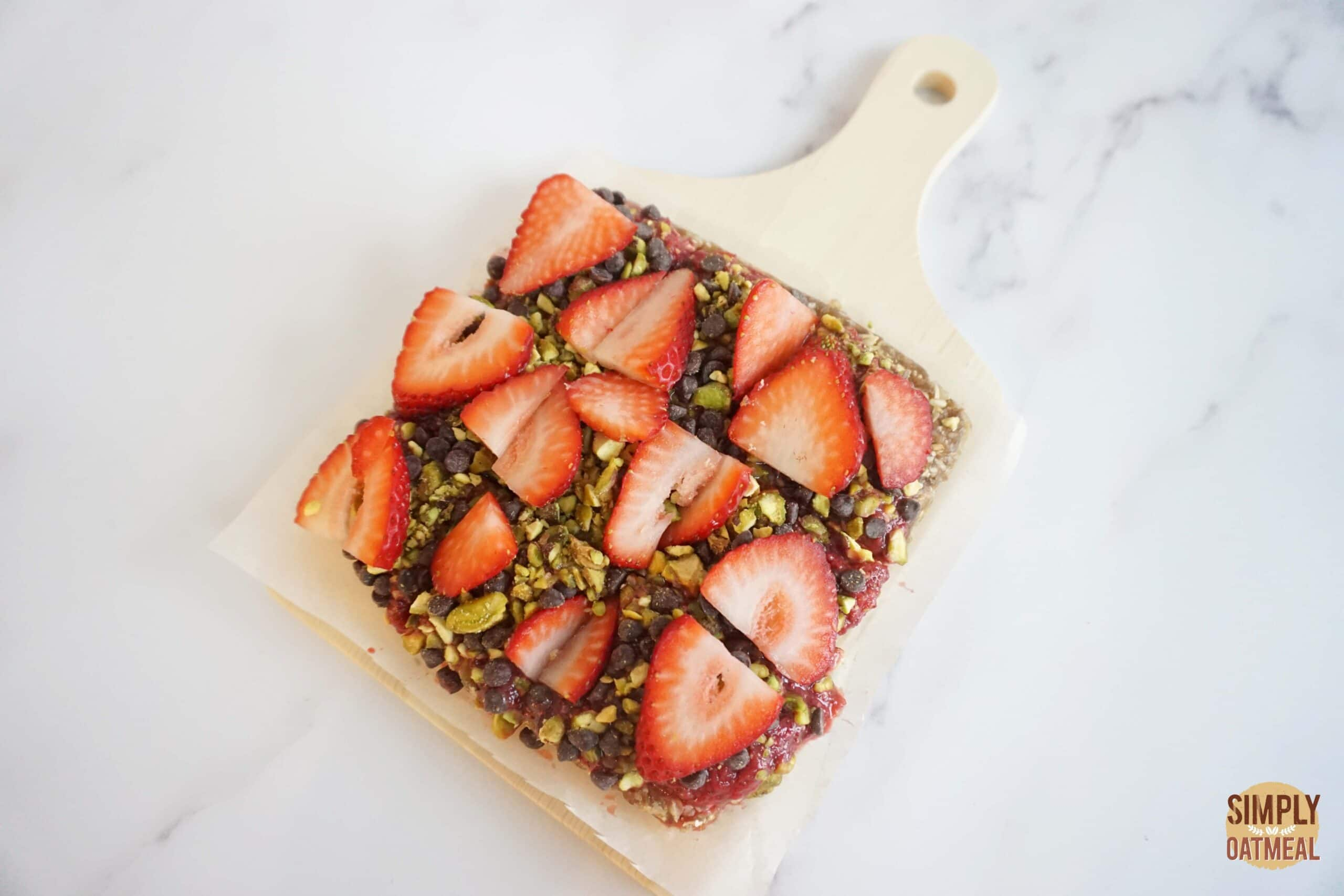No bake strawberry oatmeal bars topped with sliced strawberries, pistachios and mini chocolate chips