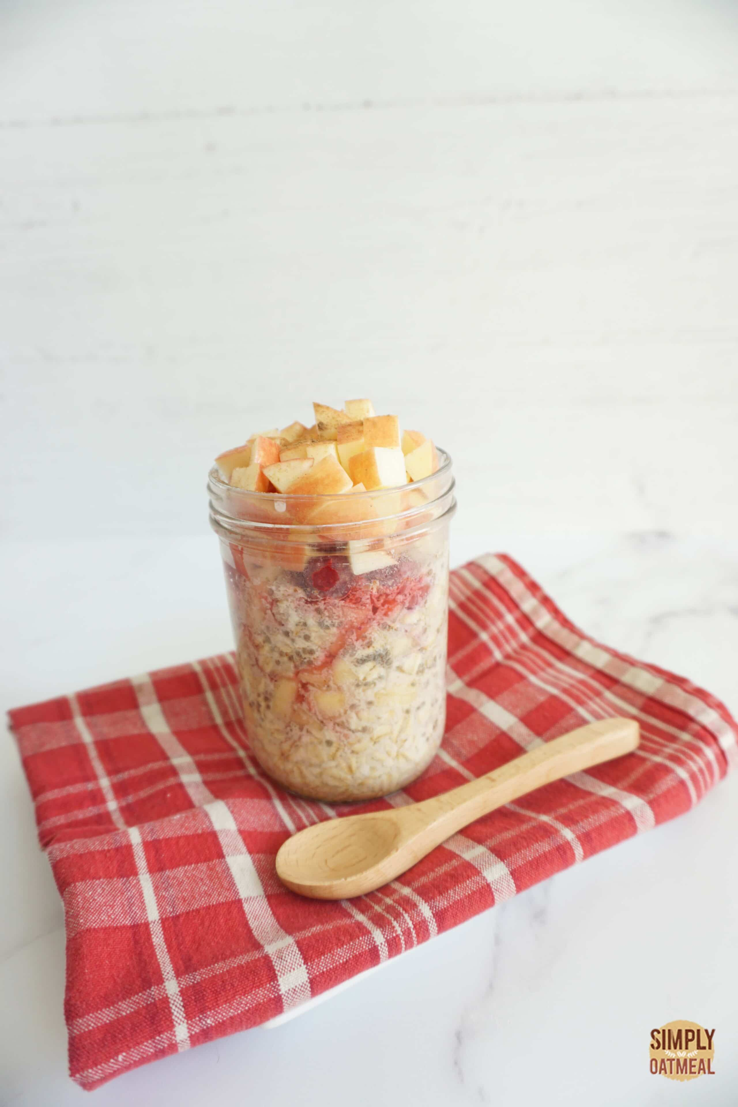 Apple raspberry overnight oats served in a mason jar with a spoon on the side