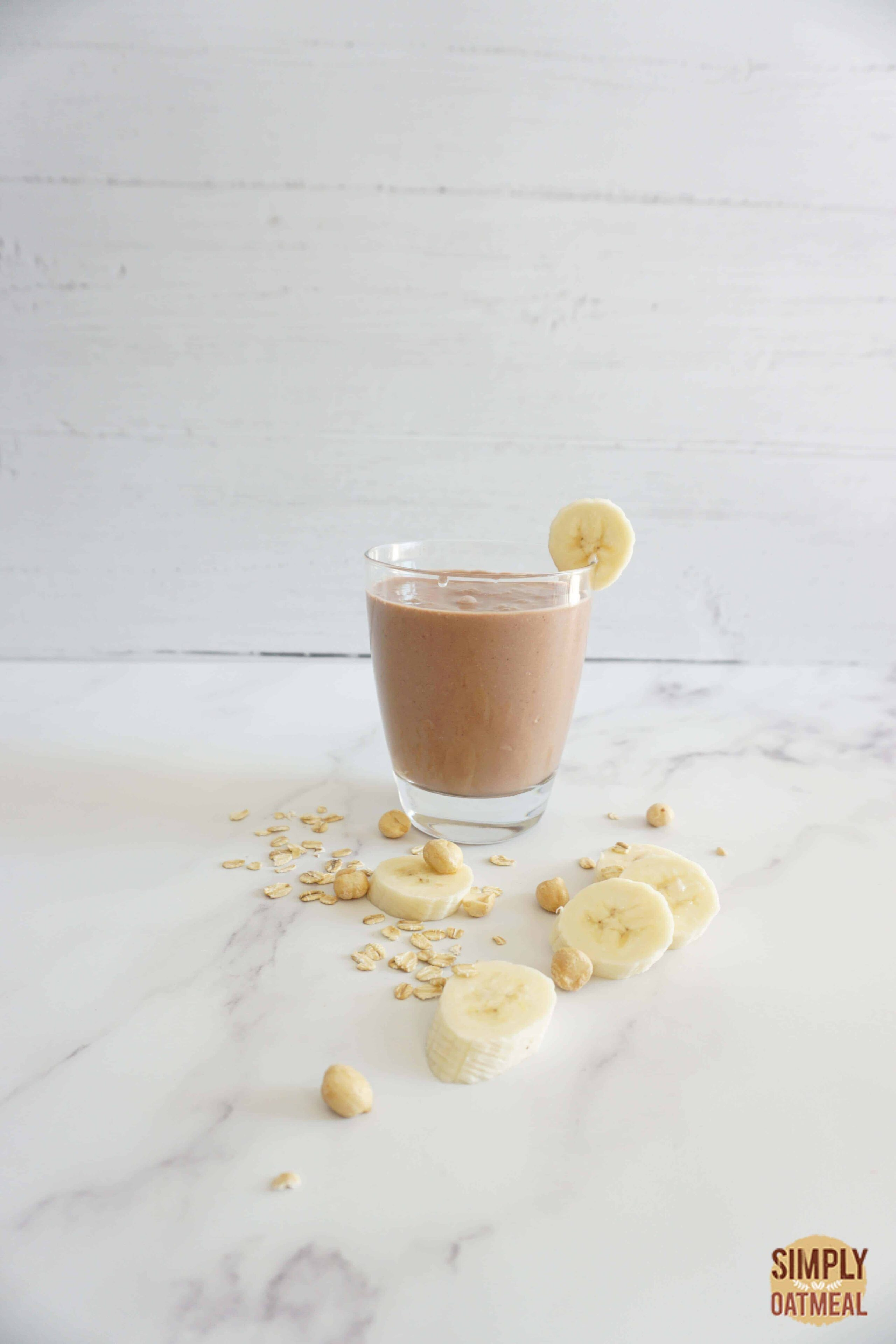 Single serving of chocolate peanut butter banana oatmeal smoothie in a glass cup