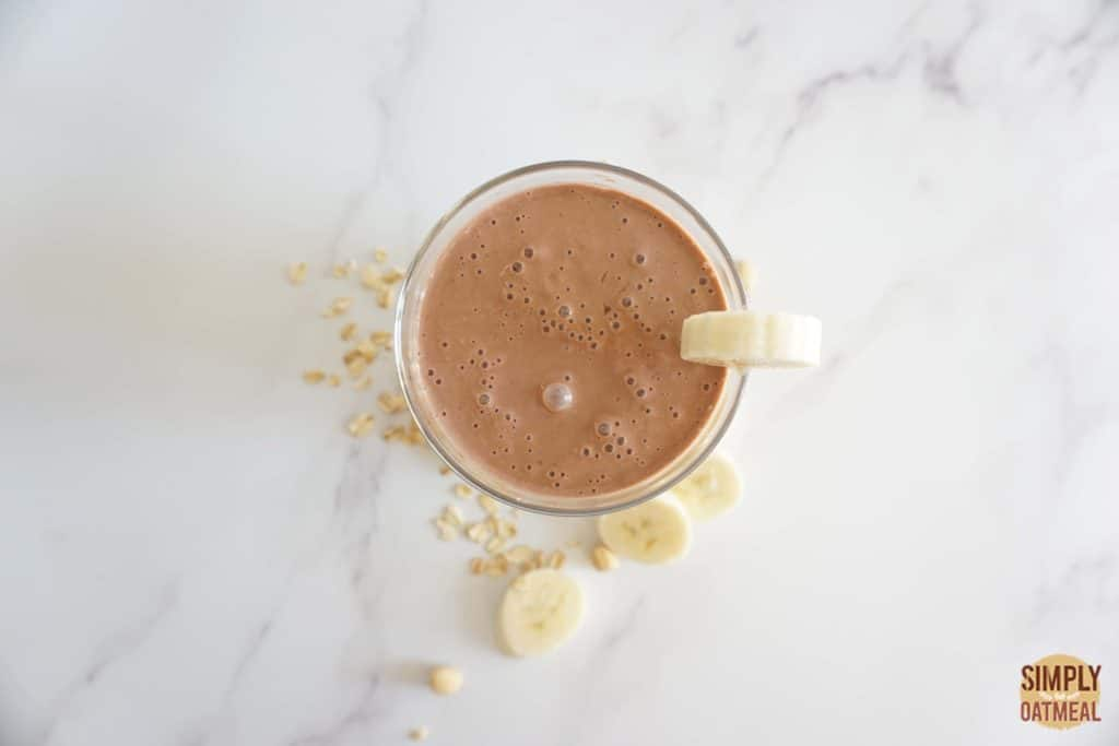 Chocolate peanut butter banana oatmeal smoothie with sliced banana on the side