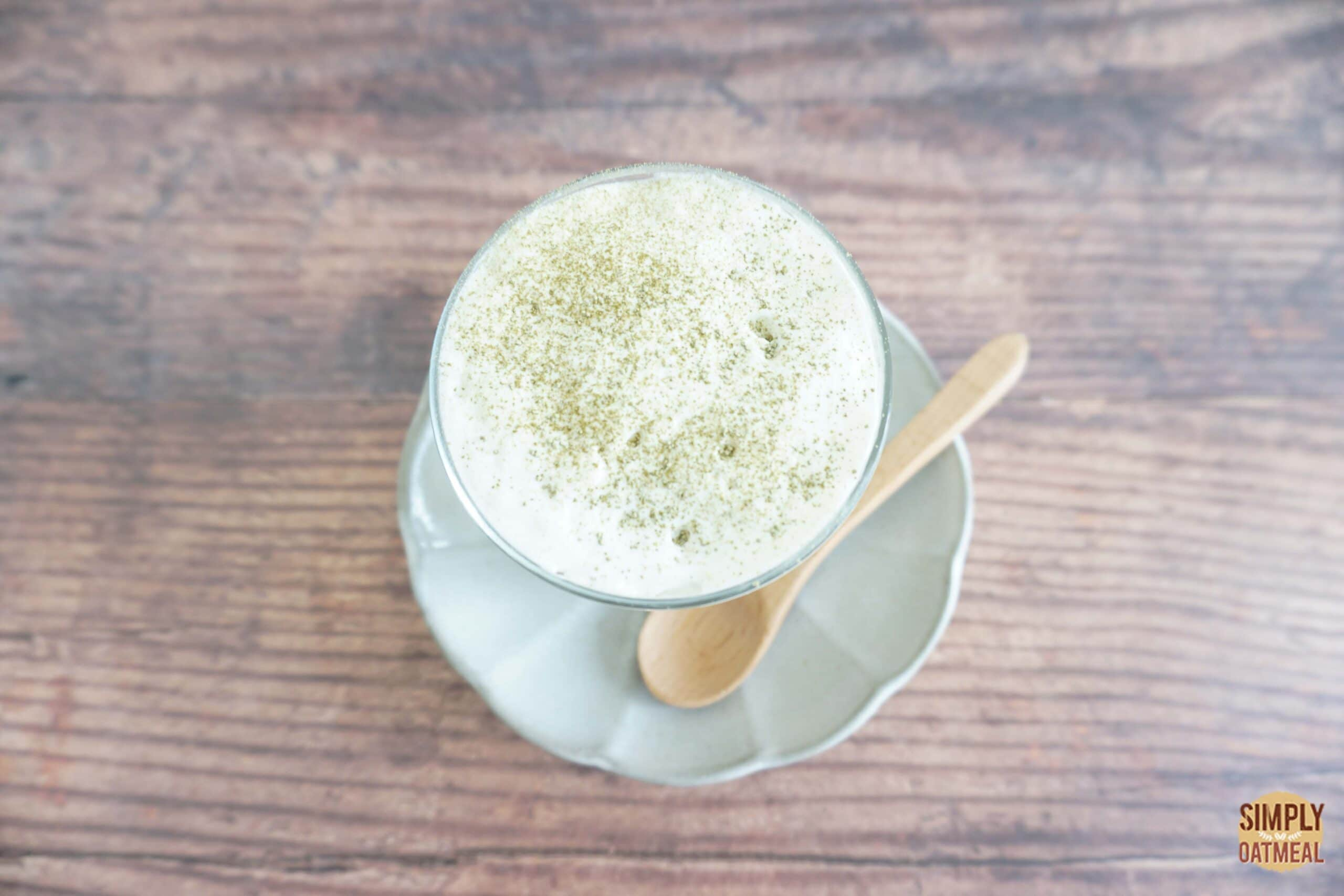 Green tea latte overnight oats topped with warm milk froth and matcha powder.