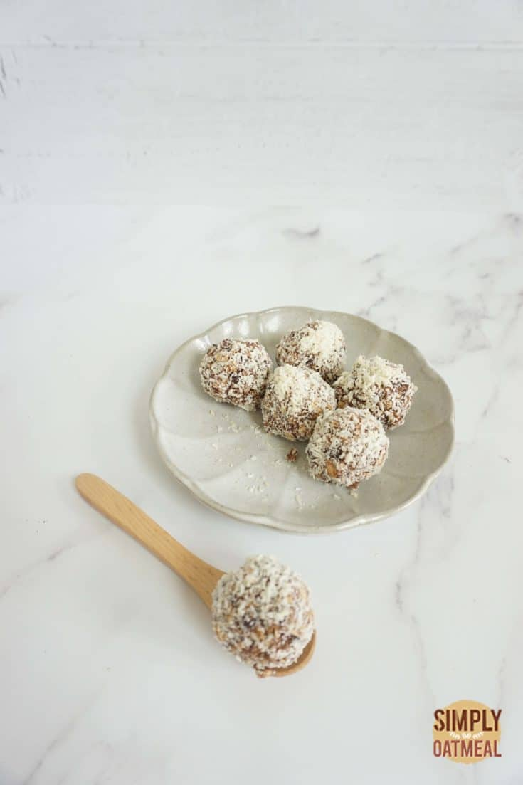 No bake almond joy oatmeal balls with a wooden spoon on the side
