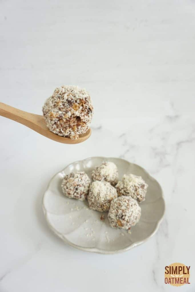 No bake almond joy oatmeal ball on a wooden spoon.