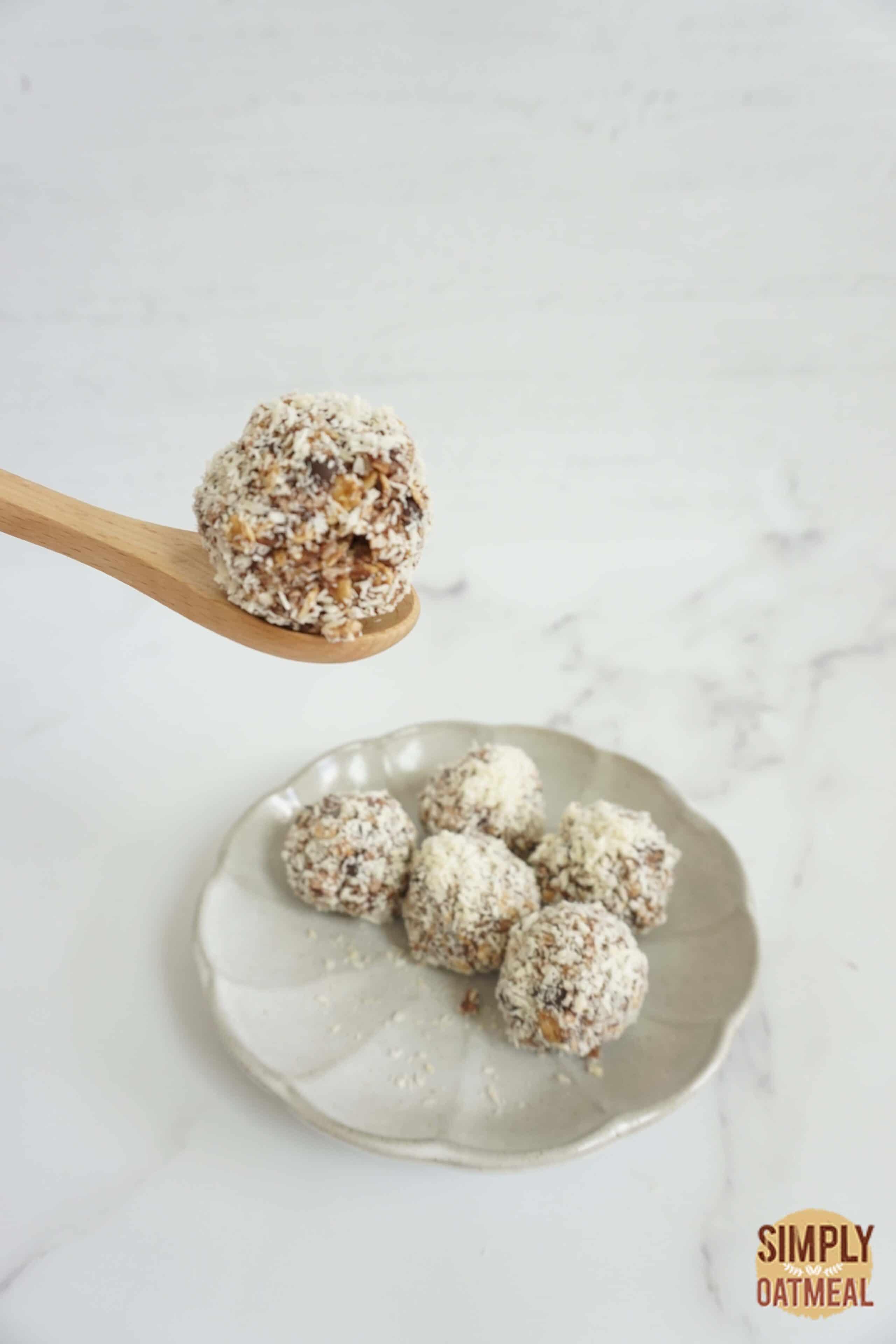 No bake almond joy oatmeal ball on a wooden spoon.