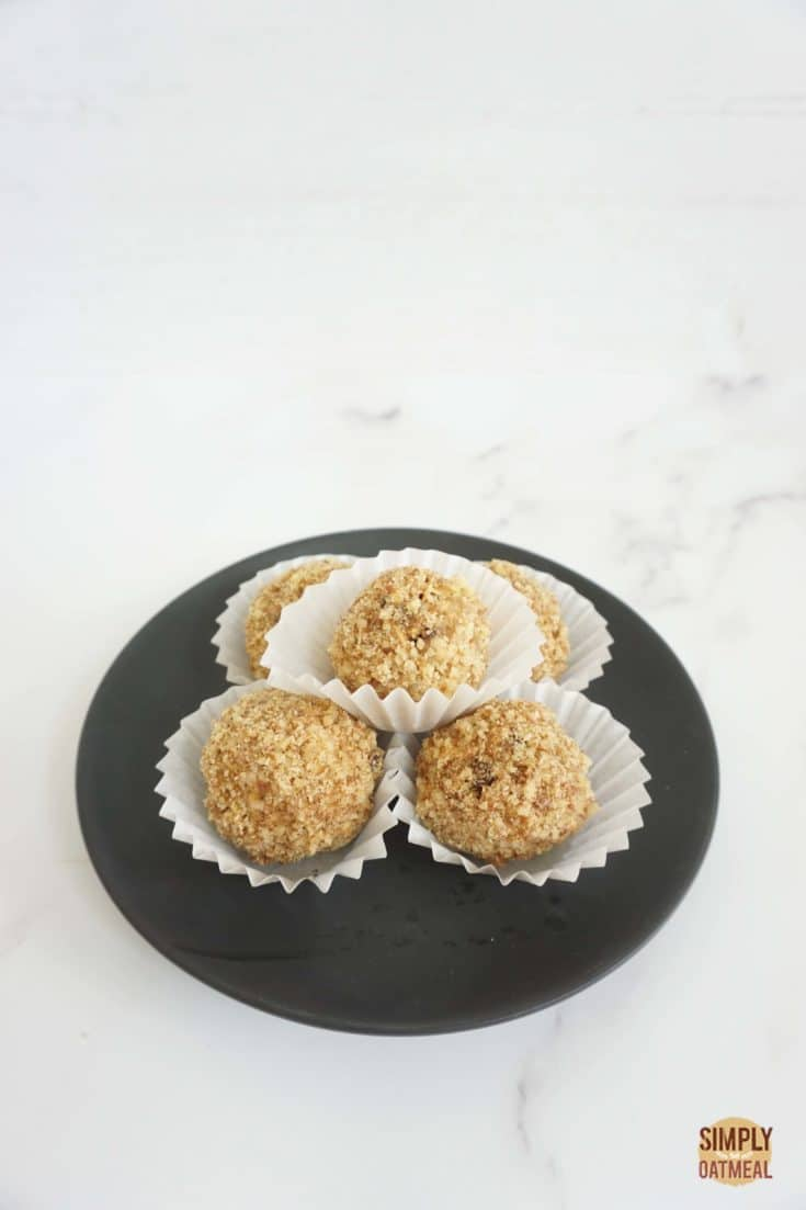 5 no bake banana walnut oatmeal balls on a black plate