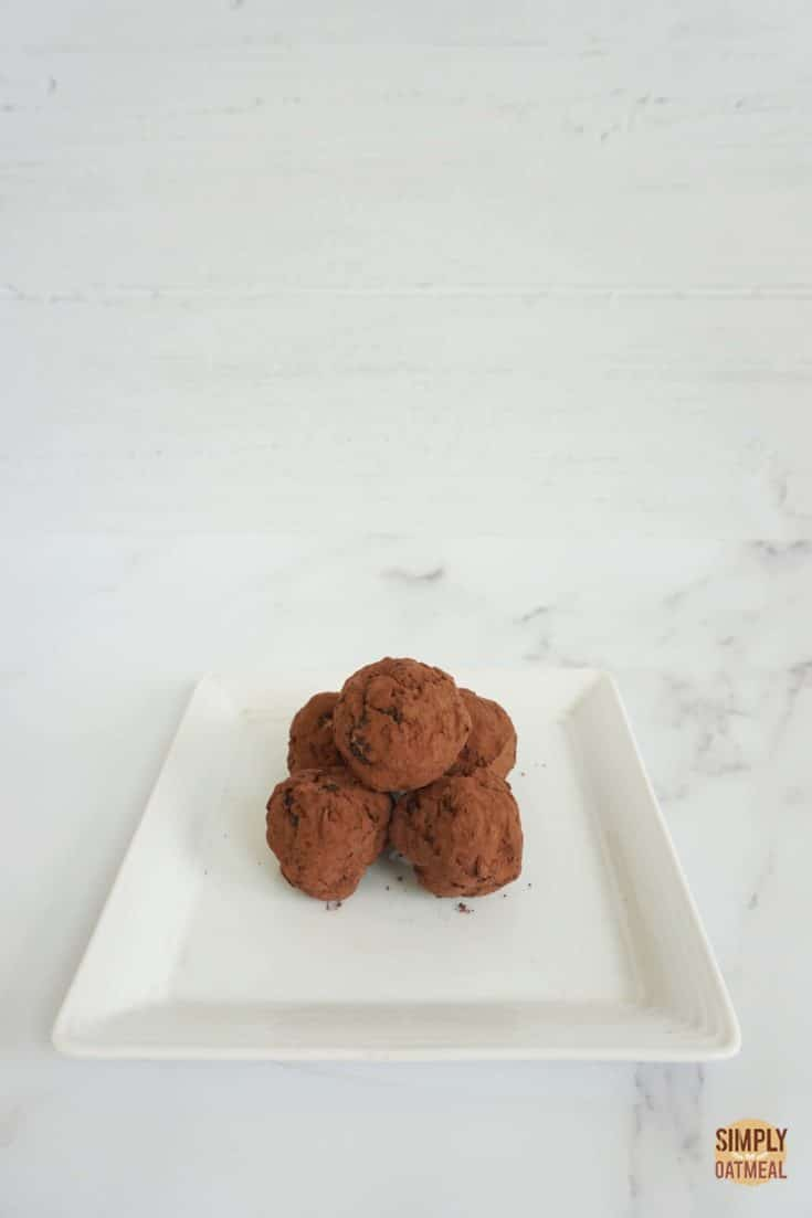 5 no bake chocolate oatmeal balls on a square white plate.