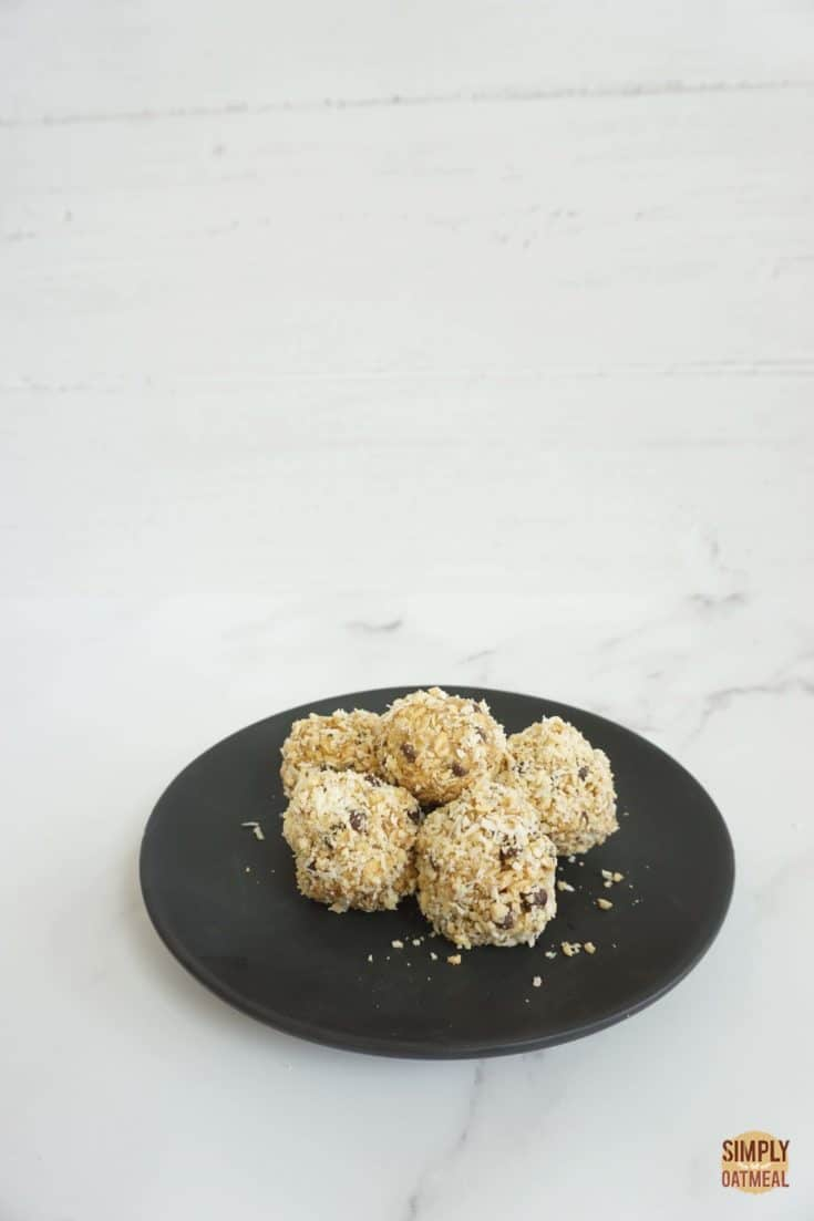 No bake peanut butter oatmeal balls on a black plate.