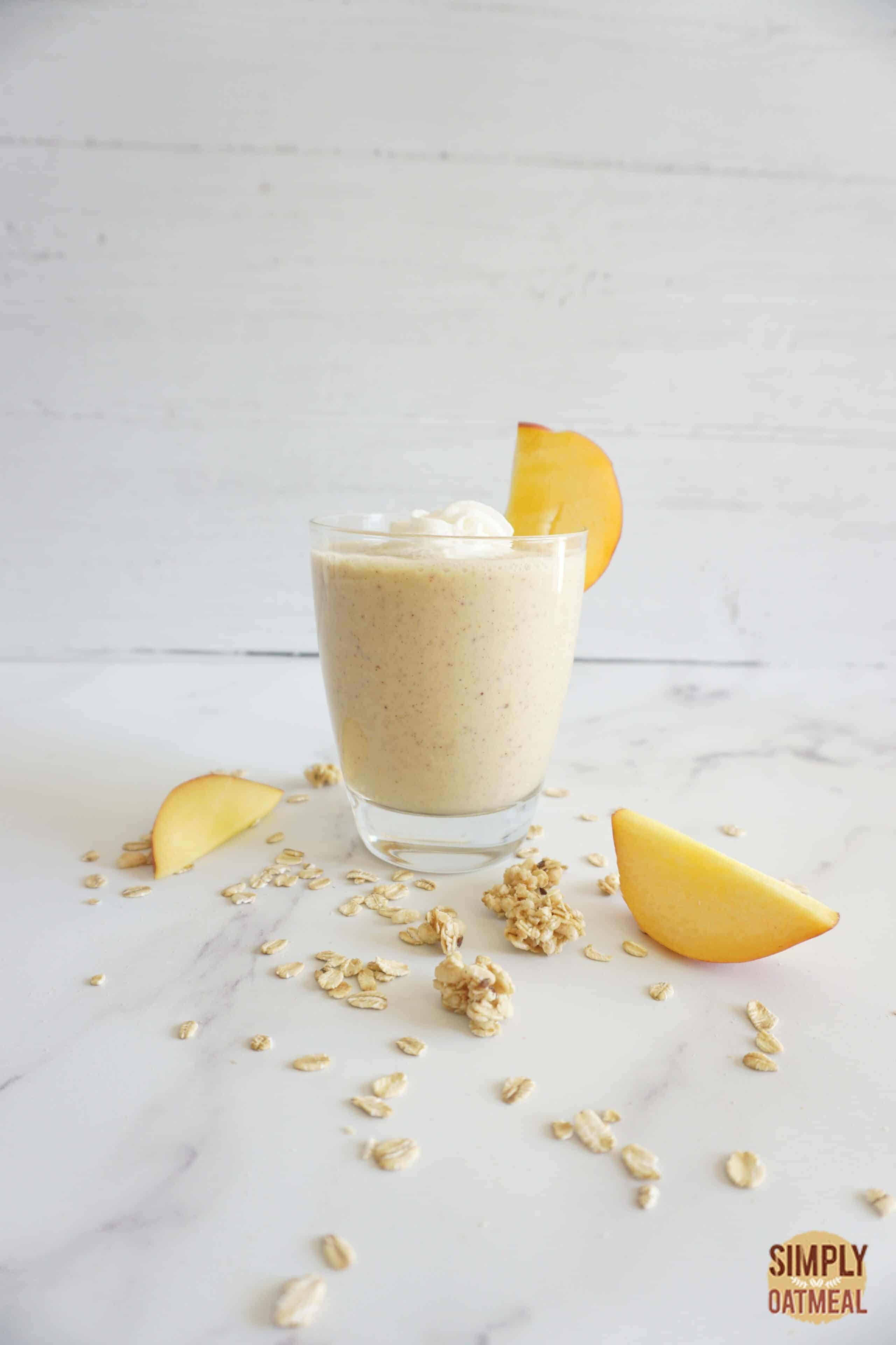 Single serving of peach cobbler oatmeal smoothie in a glass cup.